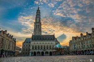 Photographie du beffroi d'Arras et de la place des héros au soleil couchant