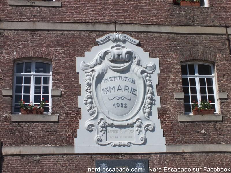 Blason sur la façade de l'école Sainte-Marie à Aire